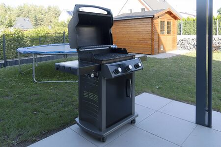 A large black gas grill stands on the street on the lawn near the house. Street cooking.