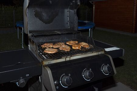 The gas grill is black, juicy meat is cooked on it. Barbecue, delicious grilled meat. Stock Photo