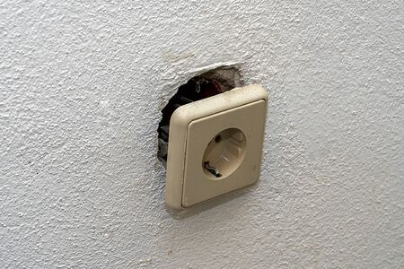 A dirty white socket fell out of the wall and hangs on wires. Repair in the house of old Euro sockets. 写真素材 - 133344175
