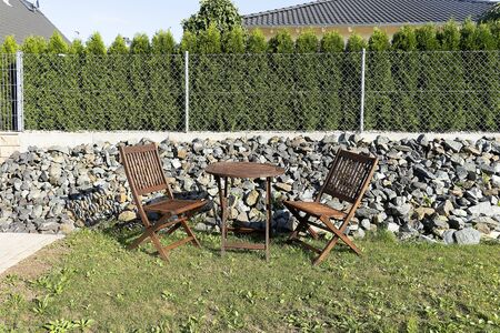 A wooden table with chairs stands outside on a green lawn. Home furniture for relaxing and eating outside. Mesh fence with stones, fence from neighbors. 写真素材 - 133344176