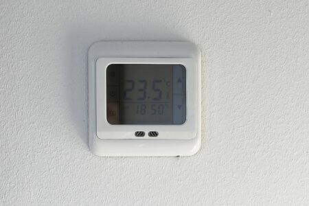 Wall-mounted display showing indoor and outdoor air temperature and heating. Smart home automation: wall-mounted temperature display on a digital thermostat. Climate control digital display on a white wall. 写真素材 - 133344174