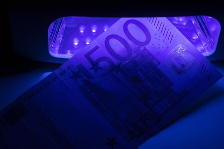 Five hundred euro paper notes on fake or genuine. Checking money on infrared light. Counterfeiting of banknotes, checking at the bank by the cashier, banking operator. Financial, banking concept, currency exchange. 写真素材 - 133344173