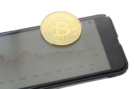 Bitcoin coin with phone, on the phone a red drop graph. Cryptocurrency is falling, loss chart. Losses in the cryptocurrency market.
