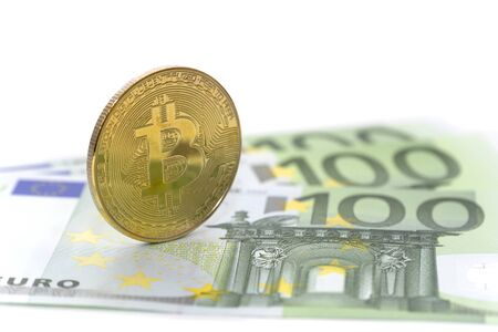Golden Bitcoin is stacked on several 100 Euro banknotes. Digital currency with 100 euros, on a white isolated background. Cryptocurrency exchange in Europe.