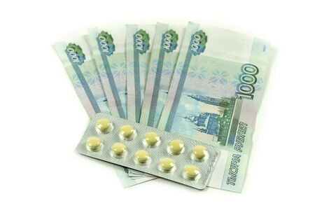 Banknotes in denominations of a thousand rubles with yellow pills. Russian money with medical supplies. Medication is expensive to buy, for treatment.