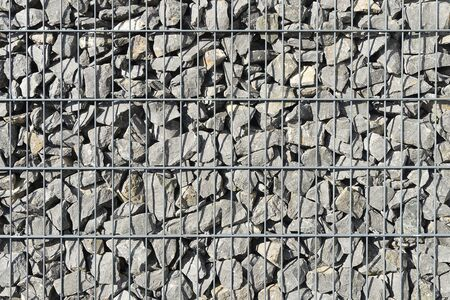 A fence of stones superimposed on a grid. Stone fence, a strong wall of small stones. Gabion made of natural stone and metal mesh for construction. Background with stone texture. 写真素材