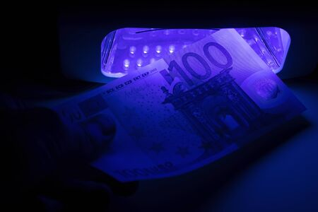 Verification of a banknote of 100 euros on a device for detecting fakes through ultraviolet light. Counterfeiting of banknotes, checking at the bank by the cashier, banking operator. 写真素材 - 134446779