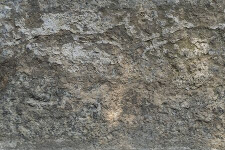 Texture of natural gray weathered stone. Background of stone covering a wall or floor texture surface with lines. Old stone with erosion.