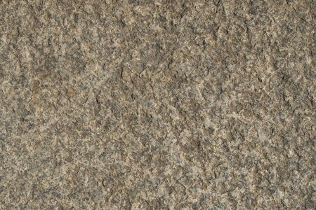 The texture of the brown stone is natural. Background of stone covering the wall or floor texture surface. Old weathered stone with erosion.