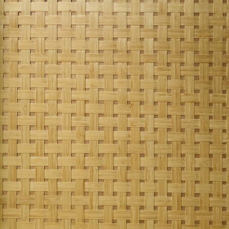 Background from wicker bamboo. Wooden planks intersect and form the texture of light brown woven bamboo. Handwork close-up.