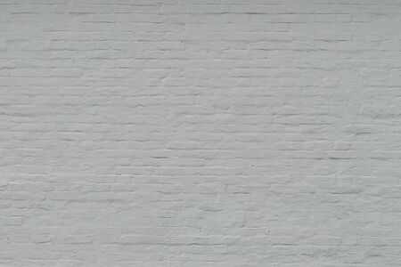 Old white painted brick wall. White background with cracked brick texture with a large layer of paint.