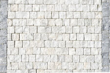 European stone pavement made of white blocks. Beautifully and evenly laid out square pavers in the city of Europe. Smooth white granite footpath.