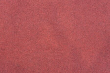 Red background, terry heavy texture. Empty fabric backdrop with dark patches. Floor covering red carpet textile.