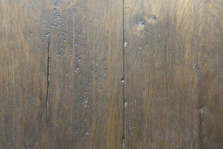 Background dark old wooden parquet floor close-up. Brown wooden background with a large texture of natural wood, coating with scratches and grooves.