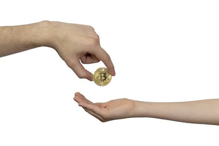 Cryptocurrency Inheritance Concept. The hand of an adult transfers gold bitcoin to the child's hand. Inheritance, translation, payment.