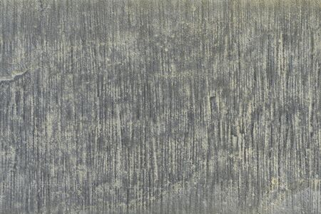 Old gray concrete slab wall close-up. Gray striped grungy surface texture, background for interior design. Weathered natural stone.