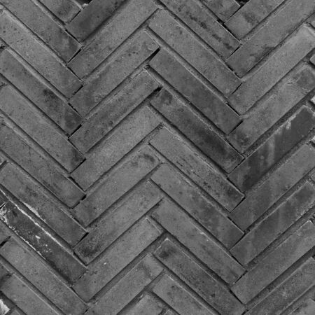 Paving blocks of rectangular blocks in black. Road pavement made of stone. A pedestrian pavement or stone path made of blocks lined with herringbone.