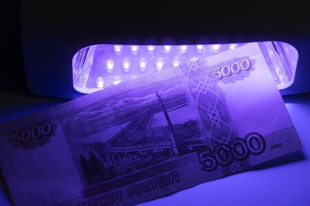 Five thousand Russian rubles in infrared light. Check on the detector. Check for fake or genuine. Counterfeiting banknotes, checking at the bank with a cashier of 5,000 rubles, by a banking operator.