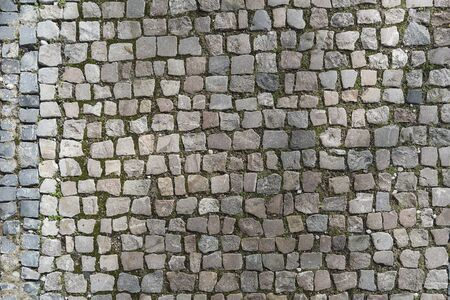 European granite cobblestone pavement with different stones. Gray stone background, textured pedestrian pavement, road in Europe.
