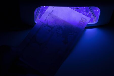 One hundred euro paper bill. Checking money on infrared light at the detector. Check for fake or genuine. Counterfeiting of banknotes, checking at the bank by a cashier of 100 euros, by a banking oper 写真素材