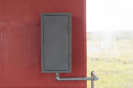 A gray iron box hangs on a red wall, next to a window. Fire box or gas box, a water or gas pipe is connected to it.
