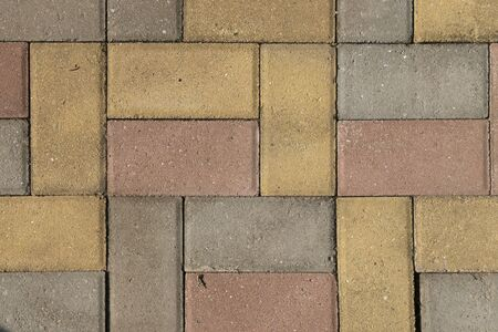 Paving blocks of rectangular blocks, color, yellow, red, gray. Road pavement made of stone. Pedestrian pavement or stone walkway made of blocks.