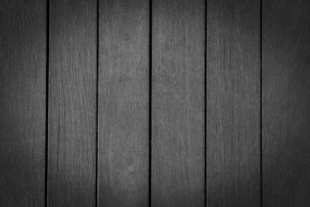 Background from black wooden vertical boards close-up. Wooden monochrome boards, texture for design. Black vignette, natural wood.