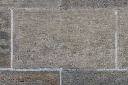Old gray wall of large concrete blocks. Closeup. Gray wall grungy surface texture. Horizontal background for interior design. 写真素材