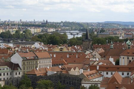 Red terracotta roofs in the city of Prague. View of the city from above, in the distance the tower, sunny day. A beautiful city for leisure and travel in Europe. Czech republic 写真素材