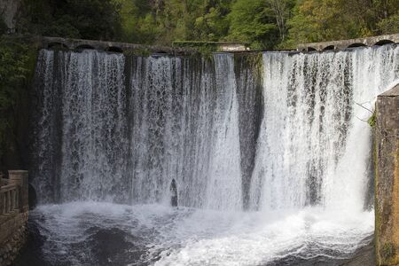 The waterfall is wide in the mountains. Beautiful water falls from the top, dam. Tourist place in the mountains.