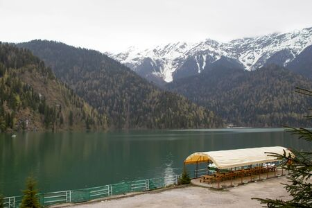 Green lake big in the mountains with snow. Mountains with trees and high mountains with snow. A beautiful place for recreation and fishing, tourism. There is a tent for food on the shore. Beautiful la