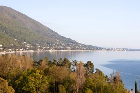 Sea coast, ocean bay. High green mountains, below the coast of the city. Top view of the blue sea. Yellow trees, autumn.