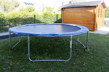 Home street trampoline on an aluminum frame, black with a blue border. Childrens trampoline for jumping is installed on the street on the green grass.
