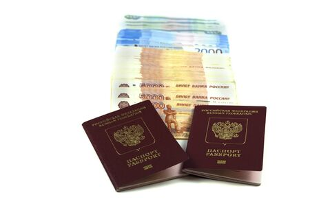 Two Russian passports with a bunch of rubles in denominations of five, two and one thousand rubles. The concept of immigration, tourism, travel to the resort. Buying a passport or a deposit, a large s 写真素材