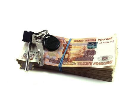 A pack of Russian rubles with a face value of five thousand rubles with the keys to the apartment. A pack of Russian money of large denominations of a million rubles. The concept of buying an apartmen