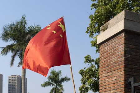 The red flag of the Republic of China flutters in the wind. Flag with yellow stars on a background of palm trees and blue sky. Six flagpole made of bamboo.