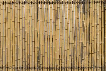 Bamboo fence texture vertical. Abstract background of wooden bamboo yellow sticks. Bamboo fence or wall texture background for interior or exterior design.