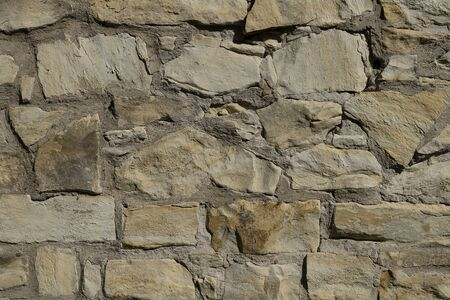 The texture is gray of natural stone, concrete surface with uneven cracked stones. A yellowish wall connected by cement, a fence. Abstraction, background for the designer.