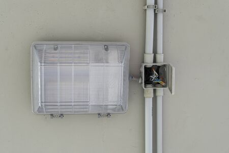 Rectangular plastic industrial street lamp, mounted on the ceiling. A modern lighting lamp is wired to an open box. Electricity safety, closed box. 写真素材