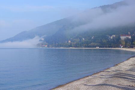 The beach is rocky with pebbles by the sea. City landscape at the bay of the sea. Morning fog, blue sea, green high mountains. Gagra Abkhazia.