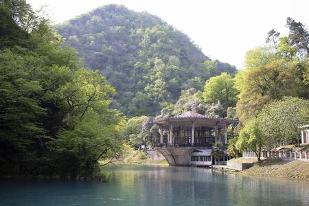 An old house is located near the water. Mountains in green trees, blue lake, green nature and palm trees, travel and tourism in Asia. Summer sunny day terrace near the water.