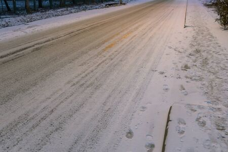 The first snow fell on the road and sidewalk. A footpath with tracks and a road for cars not cleared of snow. Winter morning snowed.
