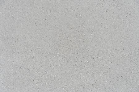 White concrete wall with a flat surface and small pores. Gray surface for design background texture.