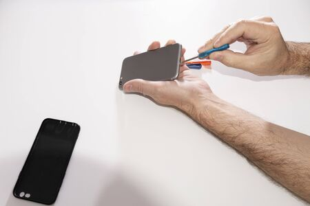 Mens hands are repairing a mobile phone. Dismantling or assembling a touch phone, repairing equipment. Phone repair in a service center.