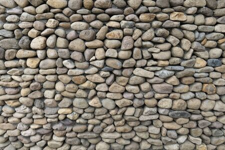 Texture for designers natural pebbles. Background of round stones, the use of texture in the design. Wall or fence made of natural stone. Peddle Stone Wall