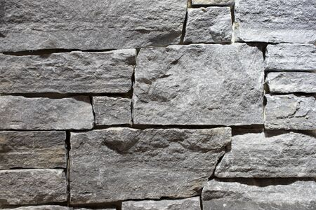 Wall made of natural gray stone. Background of stone blocks. Fence or foundation made of natural stones. Texture for design close-up.