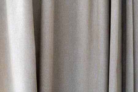 The texture of the curtains from beige fabric. Background for using texture in design. Textile curtain made of fabric close-up with pleats.