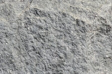 Wall of gray whole piece of granite stone. The texture of natural stone. Background for the workpiece texture designer.