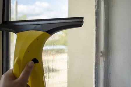 Wash the window at home with a battery wiper. The apparatus yellow collects drops of water and clean the window. Hands scrub the window. Wet glass. 写真素材