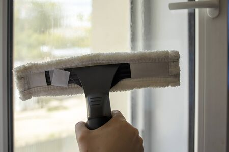 Wash the window at home with a battery wiper. The apparatus yellow collects drops of water and clean the window. Hands scrub the window. Hands wipe the glass with a soft scraper.